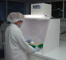 A laboratory operator is protected with a Sentry Air Systems SS-330-DCH (30″ wide ductless containment hood) during a chemical powder application.
