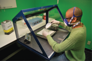 Above, a technician weighs silica on the perforated bench top of a Model 435 Portable Downdraft Bench - Sit, which pulls renegade particles down into filters that trap them below the work surface, away from his mouth and nose.