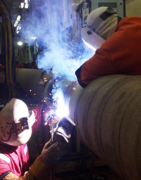 With no fume extractor in sight, two welders produce copious smoke as they weld pipe on a rig designed to lay an ultra-deep-water pipeline. Photo credit: kopf, offshore pics thread, failheap-challenge.com